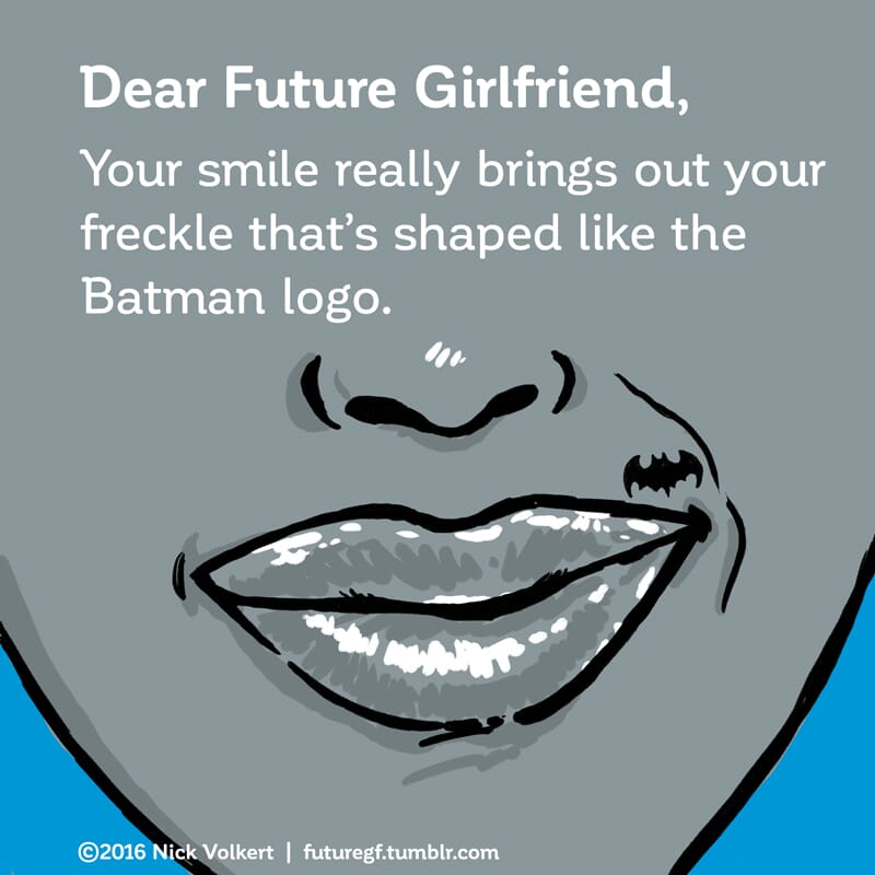 A woman smiles with a beauty mark that is in the shape of the batman logo.