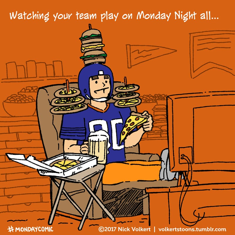 A man sits on a recliner with snacks on a helmet and shoulder pads.