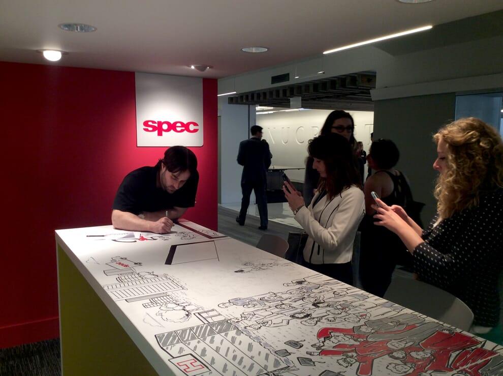 Onlookers viewing Nick Volkert working on mural for Spec Furniture in the Merchandise Mart